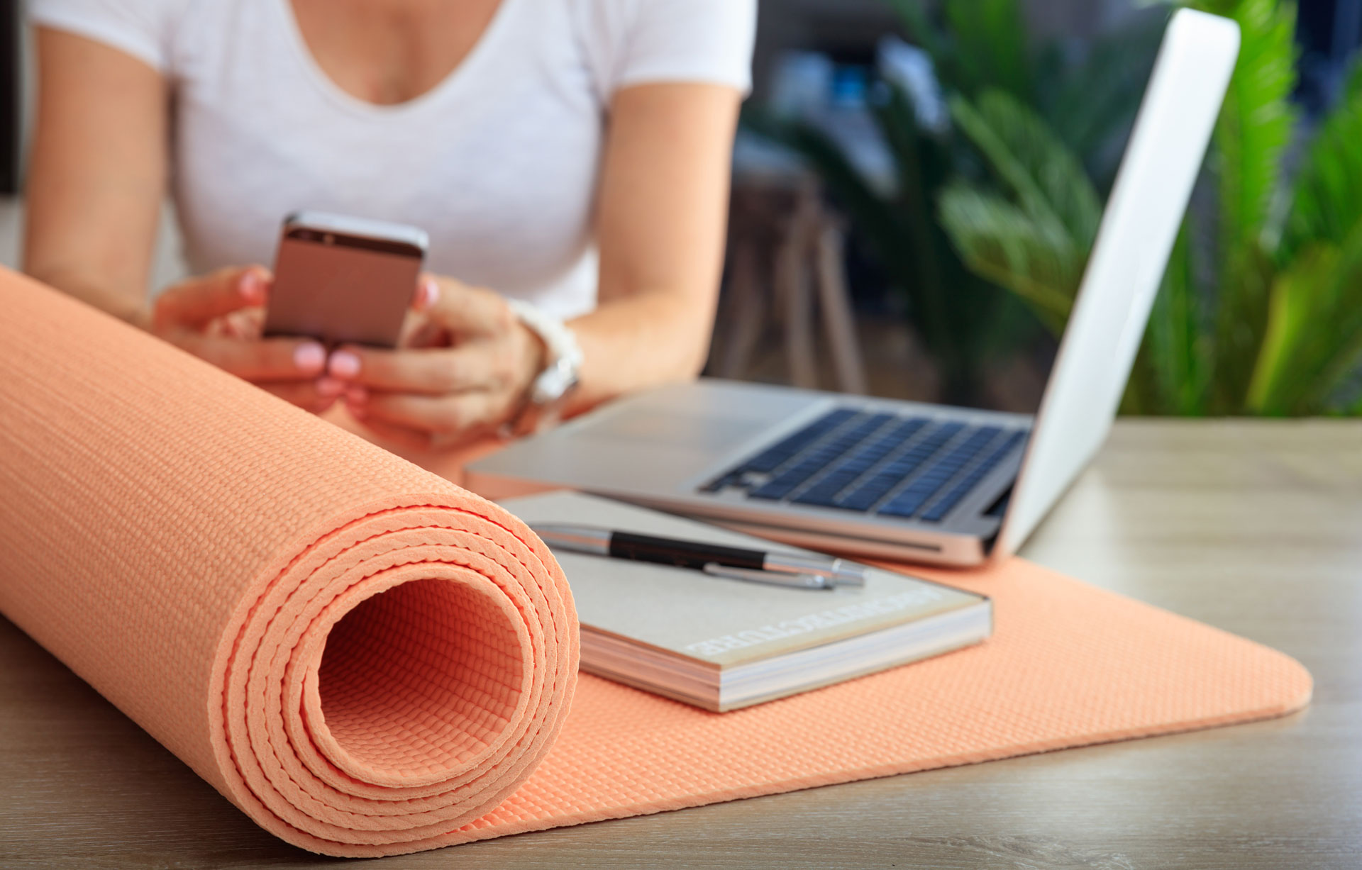 agile BGF » betriebliche Gesundheitsförderung » arbeitende Person mit Laptop, Handy, Block und Stift sowie Fitnessmatte auf dem Tisch