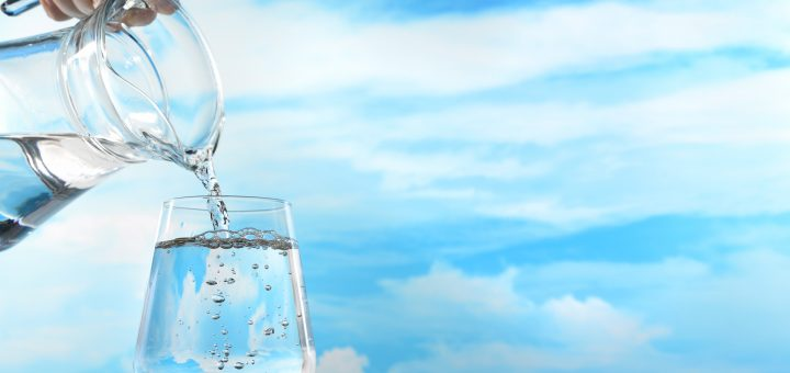 Wasser in ein Glas schütten