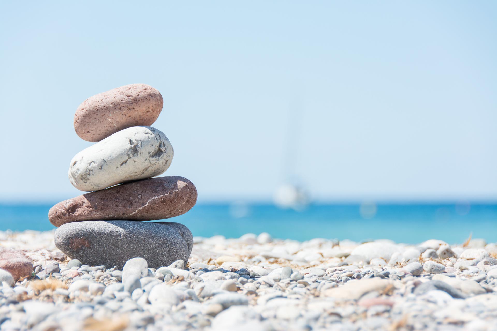 am Strand Steine gestapelt und im Hintergrund Segelboot