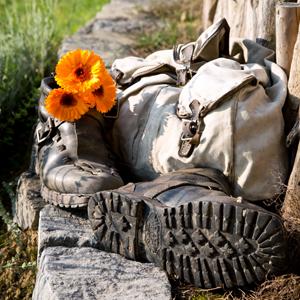 Wandern im bergischen Land - Wanderschuhe mit Rucksack liegen auf einem Mauerabsatz